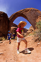 Small boy hiking under Rainbow Bridge by Lake Povel in Utah, USA