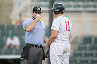 Home plate umpire Justin Anderson gets a drink of water from the Kannapolis Intimidators bat boy between innings of the game against the Greenville Drive at Intimidators Stadium on June 7, 2016 in Kannapolis, North Carolina.  The Drive defeated the Intimidators 5-2 in game two of a double header.  (Brian Westerholt/Four Seam Images)