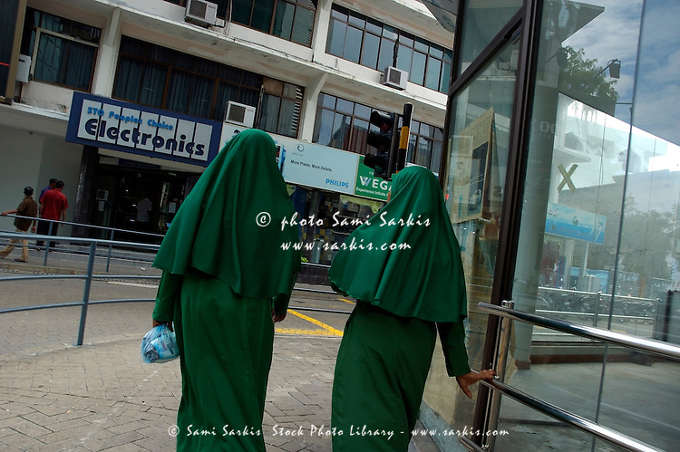Two women walking downtown wearing the traditional Islamic dress, Male, Maldives.