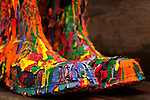 Boots covered with multicolored dripping peeling paint close up