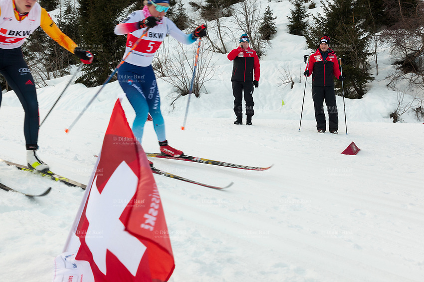 Switzerland. Canton Ticino. Swiss-Cups Campra. Cross Country Skiing. FIS Classic Sprint Race. Hippolyt Kempf  (R) is the Cross Country Skiing Chef by Swiss-Ski. He stands in the snow holding two ski poles and watches the race. Bernhard Aregger (C) , the CEO of Swiss-Ski, talks on his mobile phone. Hippolyt Kempf (born 10 December 1965) is a Swiss Nordic combined skier who competed during the late 1980s and early 1990s. He won a complete set of Olympic medals, earning two of them at the 1988 Winter Olympics in Calgary (gold: 15 km individual, silver: 3 x 10 km team) and the third at the 1994 Winter Olympics in Lillehammer (bronze: 3 x 10 km team). Kempf also earned a 3 x 10 km team silver medal at the 1989 FIS Nordic World Ski Championships in Lahti. A German and a Swiss competitor schusses down the mountain. Athletes are trained to achieve endurance, strength, speed, skill and flexibility at different levels of intensity. A swiss flag used by Swiss-Ski as symbol of its belonging to Switzerland. Swiss-Ski is a branch of Swiss Olympic. The Fédération Internationale de Ski (FIS; English: International Ski Federation) is the world's highest governing body for international winter sports. Founded  on 2 February 1924, it is responsible for the Olympic disciplines of cross-country skiing. The FIS is also responsible for setting the international competition rules. 4.01.2020 © 2020 Didier Ruef