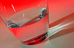 Glass of water against a red background. Royalty Free
