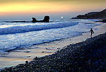 Surfer walks along El Tunco beach on the Pacific in El Salvador with a rising moon.  El Tunco is named after the rock formation seen in the photograph.