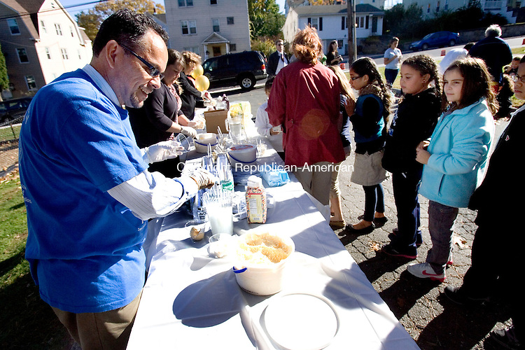 WATERBURY, CT. 16 October 2012-101612SV13-Edwin Rodriguez, development officer of the Connecticut Community Foundation, scoops ice cream at Chase Park in Waterbury Tuesday. The Foundation hosted the ice cream social at Chase Park Playground to thank the community volunteers who helped build the new playground in June. .Steven Valenti Republican-American
