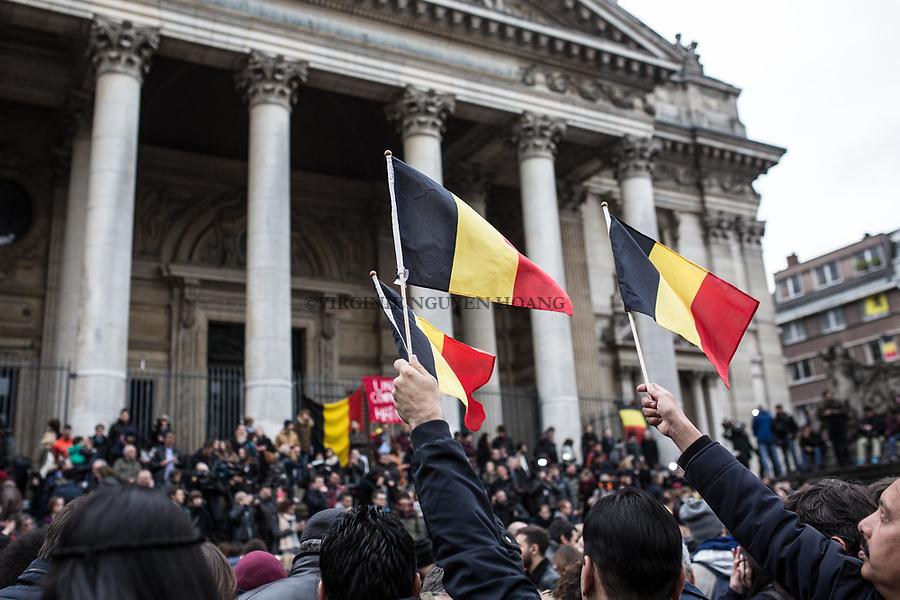 BRUXELLES, Belgique: Drapeaux belges après la minute de silence en face de la Bourse, le 23 mars 2016. 31 personnes sont mortes et 300 ont été blessées dans les attentats commis à Zaventem et dans la station du métro bruxellois Maelbeek, selon le dernier bilan du Centre de crise. Dans le centre de Bruxelles, des centaines de personnes se rassemblent en commemoration aux victimes.