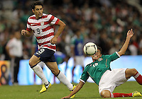 MEXICO CITY, MEXICO - AUGUST 15, 2012:  Herculez Gomez (9) of the USA MNT sends the ball past Hector Moreno (15) of  Mexico during an international friendly match at Azteca Stadium, in Mexico City, Mexico on August 15. USA won 1-0.