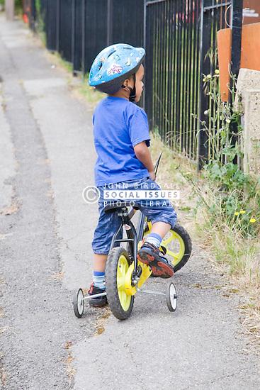 Little boy learning to ride a bike,