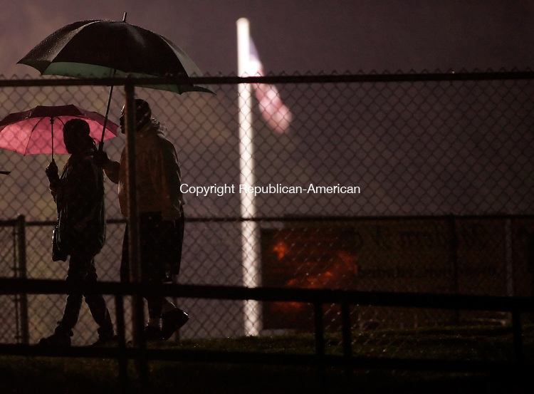 Waterbury, CT- 30, September 2011-093011CM04  A couple leaves the Watertown football field Friday night.  Thunderstorms ripped through the area, forcing officials to postpone the game against Wilby.  Christopher Massa Republican-American