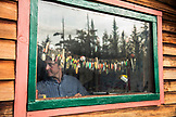 USA, Alaska, Homer, China Poot Bay, Kachemak Bay, owners son fixing the collection of fishing lures at the Kachemak Bay Wilderness Lodge