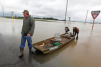 "From left, Steve Hyten, April Gensler and Josh Sherfield cross the westbound lanes of US 60 with their boat in-tow in Essex, MO on Wednesday, April 27, 2011. The group unsuccessfully tried to reach Gensler's home to collect some belongings left behind during evacuation the day before. ""The current was just too strong for our motor,"" said Gensler. ""If the current wasn't so bad, we would've made it."""