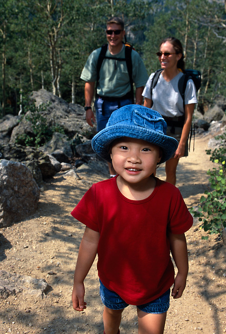 Young girl leads couple hiking on mountain trail, Rocky Mtn Nat'l Park, CO