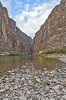 Santa Elena Canyon Vertical - A verticle view of Santa Elena Canyon as the Rio Grande river flow out of mountains that separate Texas from Mexico.  This Texas landscape had a nice blue sky with some nice clouds and I like the way the river rocks led your eyes inside the canyon.