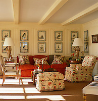 A large collection of ornithological prints is displayed on the wood panelled walls of the living room