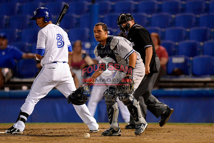 Tampa Yankees catcher Francisco Arcia looks to third after blocking a ball in the dirt as Gabe Jacobo #8 and umpire Fernando Rodriguez look on during a game against the Dunedin Blue Jays on April 11, 2013 at Florida Auto Exchange Stadium in Dunedin, Florida.  Dunedin defeated Tampa 3-2 in 11 innings.  (Mike Janes/Four Seam Images)