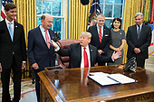 "United States President Donald J. Trump makes remarks prior to signing S. 3508, the ""Save Our Seas Act of 2018"" in the Oval Office of the White House in Washington, DC on Thursday, October 11, 2018.  Pictured from left to right: Acting NOAA Administrator Admiral Tim Gallaudet; US Secretary of Commerce Wilbur L. Ross, Jr.; President President Donald J. Trump; US Senator Dan Sullivan (Republican of Alaska); Julie Fate, wife of Senator Sullivan; and US Senator Sheldon Whitehouse (Democrat of Rhode Island).<br /> Credit: Ron Sachs / CNP"