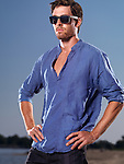 Fashion portrait of a young man wearing a blue shirt and sunglasses at the beach