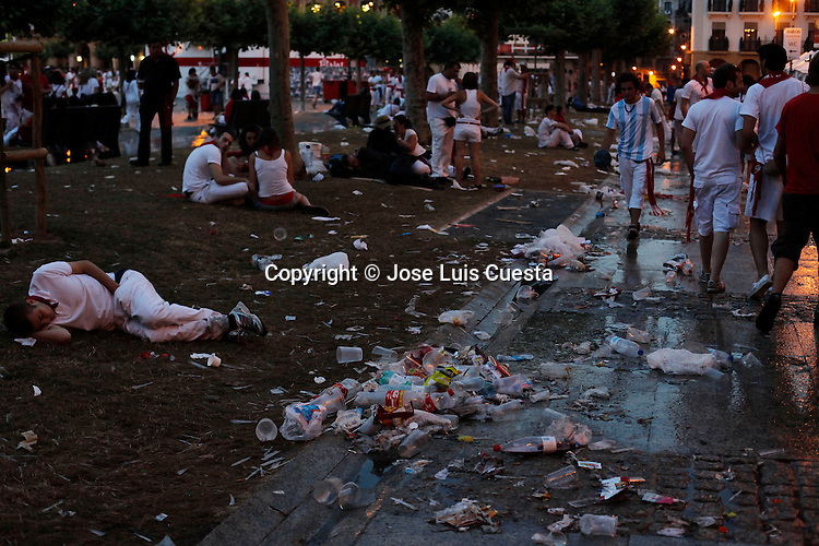 Trash accumulates at square of Pamplona after night party during San Fermin. Every night many people and revelers make the party at the street, in Pamplona, Spain. San Fermin festival is worldwide known because the daily running bulls.