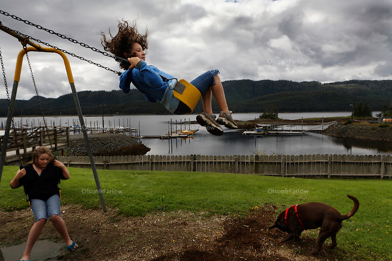 Young girls gather in community park in Thorne Bay to swing in the summer before school starts.