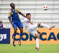 Jose Barralaga (13) of Honduras clears the ball away from Jabarry Chandler (11) of Barbados  during the group stage of the CONCACAF Men's Under 17 Championship at Catherine Hall Stadium in Montego Bay, Jamaica. Honduras defeated Barbados, 2-1.