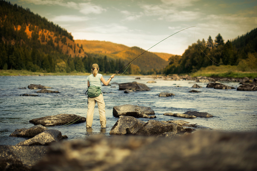 A trout fisher casts for rainbow trout as the sun sets on the Kootenai River near Libby, Montana.