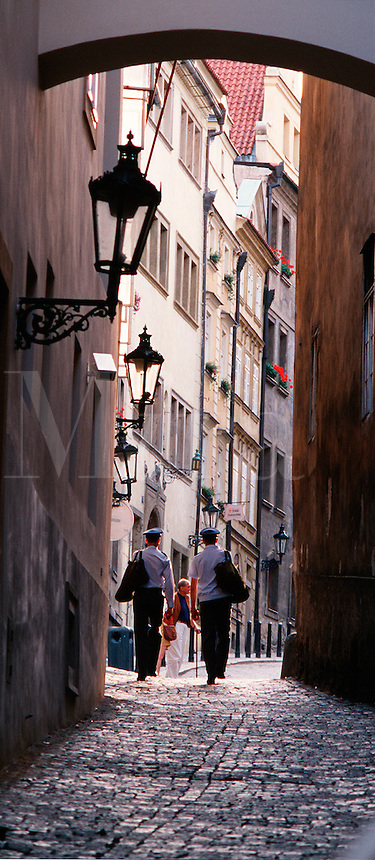 People walk down a cobbled alleyway between buildings. Prague, Czech Republic.