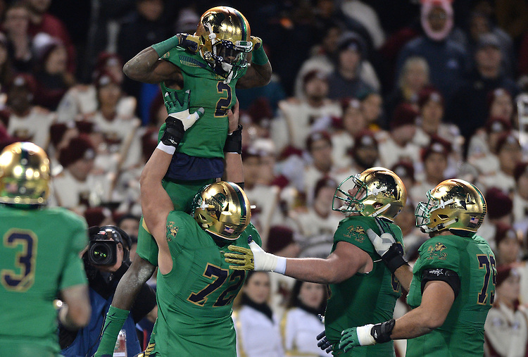 (Boston, MA, 11/21/15) Notre Dame's Chris Brown (2) leaps into the arms of teammate Nick Martin after Brown scored a third quarter touchdown against Boston College at Fenway Park in Boston on Saturday, November 21, 2015. Photo by Christopher Evans