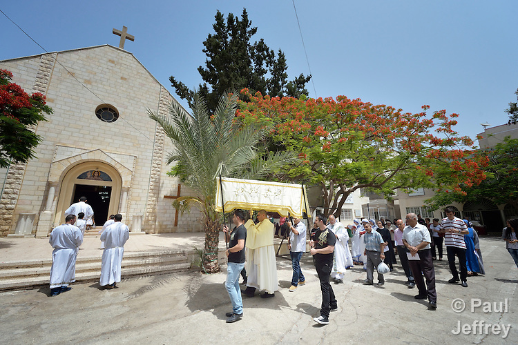 Father Jorge Hernandez, under the awning, leads a Corpus Christi procession outside the Holy Family Catholic Parish in Gaza City. Father Hernandez is Argentinian, and a missionary of the Argentina-based Institute of the Incarnate Word.