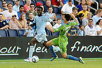 Kei Kamara (23) midfielder Sporting KC waiting for the tackle from Alvaro  Fernandez (15) midfielder Seattle Sounders... Sporting Kansas City were defeated 1-2 by Seattle Sounders at LIVESTRONG Sporting Park, Kansas City, Kansas.