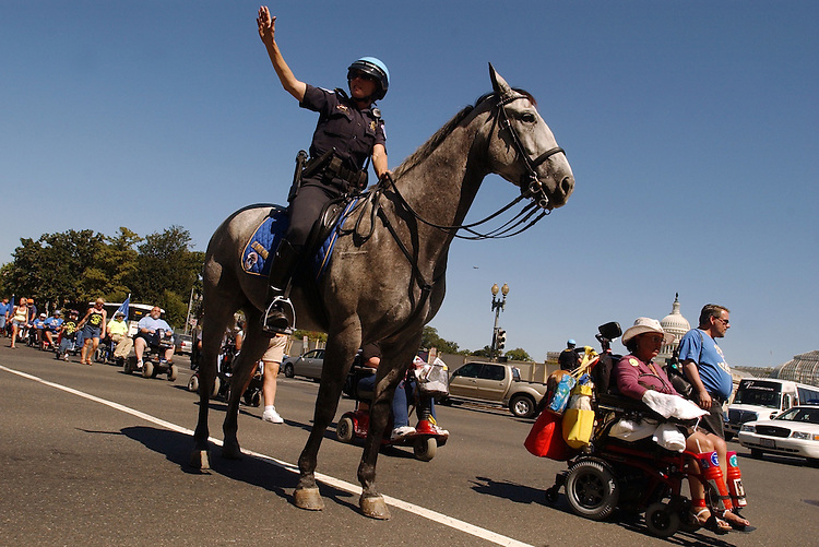 "Sgt. Kathleen Bignotti atop horse ""Freedom,"" holds up traffic while while ADOPT protesters cross Independence Avenue.  Today was the last day of the Capitol Police Mounted Unit."