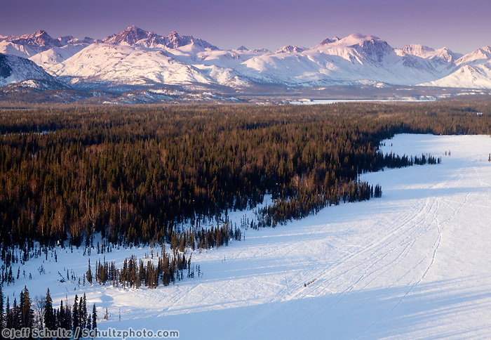 Jodi Bailey runs down a slough on the way to the Finger Lake checkpoing with the Alaska Range in the background during Iditarod 2011