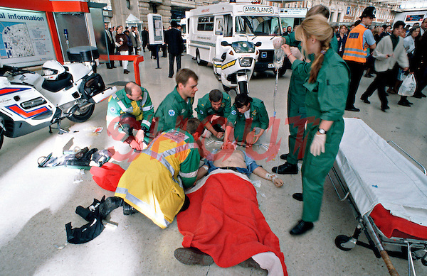 Paramedic ambulance crews attend a cardiac arrest victim on a train station platform. A paramedic is preparing to use the paddles of a defib to shock the victim. The rapid response paramedic motorcycle can be seen in the background. This image may only be used to portray the subject in a positive manner..©shoutpictures.com..john@shoutpictures.com