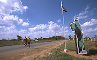 06 FEB 2003 - SANCTI SPIRITUS, CUBA - Participants run past a Cuban flag and a billboard of Fidel Castro during the Ruta Ecologica. (PHOTO (C) NIGEL FARROW)