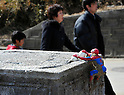 March 11, 2012, Rikuzentakata, Japan - People go by the gatepost of a local household where a Spiderman doll is attached in  Rikuzentakata, Iwate Prefecture, some 402 km northeast of Tokyo, on Sunday, March 11, 2012..Memorial ceremonies were held throughout Japan to mark the one year anniversary of the massive earthquake and tsunami that struck the country?fs northeastern region, killing just over 19,000 people and unleashing the world?fs worst nuclear crisis in a quarter century. The quake was the strongest recorded in the nation?fs history, and set off a tsunami that towered more than 65 feet in some spots along the northeastern coast, destroying thousands of homes and wreaking widespread destruction. (Photo by Natsuki Sakai/AFLO) AYF -mis-