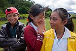 Three smiling Guatemalan children pose near their church in San Nicolas, Ixil, Western Highlands, Guatemala