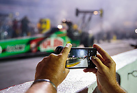 Aug 31, 2018; Clermont, IN, USA; Detailed view as a media rep uses an iPhone camera phone to take a picture as NHRA top fuel driver Leah Pritchett does a burnout during qualifying for the US Nationals at Lucas Oil Raceway. Mandatory Credit: Mark J. Rebilas-USA TODAY Sports