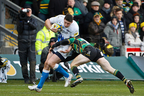 24.12.2011.  Northampton, England. Jack CUTHBERT of Bath Rugby is tackled by Jamie ELLIOTT of Northampton Saints during the Aviva Premiership match between Northampton Saints and Bath Rugby at Franklin's Gardens.