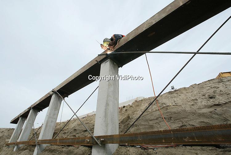 Foto: VidiPhoto..HERVELD - Bij het klaverblad Valburg (A15/A50) worden zes nieuwe viaducten naast elkaar aangelegd om de Betuwelijn ongehinderd en gelijkvloers doorgang te kunnen bieden. Vier viaducten worden aangelegd door onder het verhoogde snelwegtalud van de A50 door te graven. De ontstane doorgang onder de hoofdrijbaan en rangeerwegen wordt vervolgens verstevigd en omgebouwd. Daarnaast komen twee viaducten voor de verbindingsbogen (op- en afritten). De oostelijke zijde is half april klaar. Op dit moment wordt er geasfalteerd. Bijzonder is ook dat de bekisting onder de rijbaan wordt doorgetrokken naar de westzijde voor hergebruik om zo kostbare tijd te besparen. Het verkeer wordt tijdelijk over de andere rijbaan geleid. Eind dit jaar moet de voor Nederland unieke constructie gereed zijn.