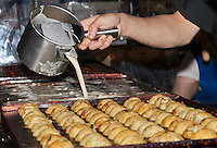 After adding the octopus, the chef then poured on enough batter to fill the pan.  Chef Ryota Akai of Japan, seen during a takoyaki cooking demonstration at Mitsuwa Market in Costa Mesa, CA.