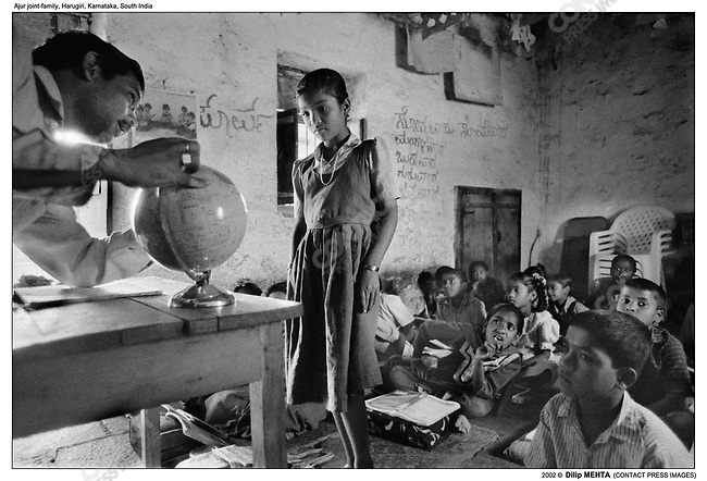In one of the two classrooms a teacher uses a globe to conduct a lesson in Geography. The student standing is from the family as are a number of others in the classroom.