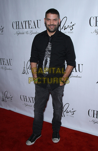 Guillermo Diaz.Brit Morgan celebrates her birthday at Chateau Nightclub inside Paris Las Vegas, Las Vegas, Nevada, USA..October 1st, 2011.full length black shirt jeans denim tie hands in pockets beard facial hair .CAP/ADM/MJT.© MJT/AdMedia/Capital Pictures.