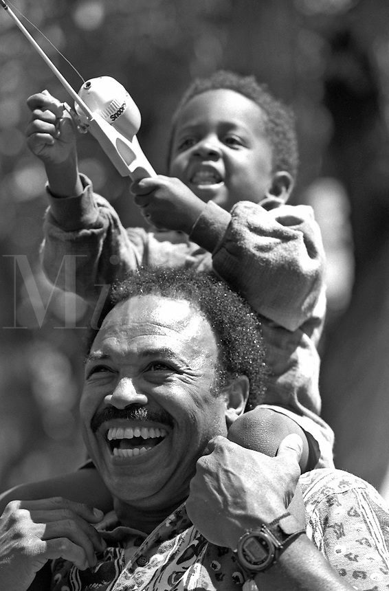 African-American Father with young son on shoulders, fishing; smiling; laughing; family activities, parents, children, Black child, man, black and white image. Dave Johnson, Gus Hoffman. Colorado, park.