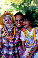 Two children wearing lei and dressed in 'The Wizard of Oz' costumes clown around with a local man.