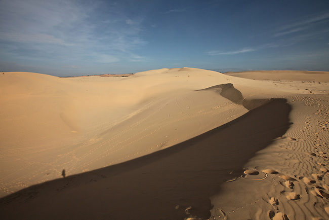 A lone silhouette is visible at the bottom of a hill at the white dunes, about 30 kilometers north of Mui Ne, Vietnam. Nov. 16, 2011.