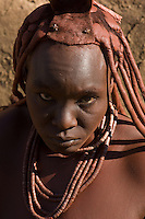 The Himba are a minority group in Namibia, representing less than one per cent of the population. They cover their skin with a red dust and, since their hair naturally grows only very short, the women attach extensions of animal hair with an adhesive made from the same dust.