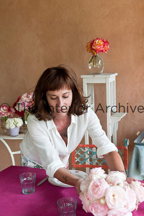 Maddalena Caruso applies the last touches to the bowl of roses in the middle of the table