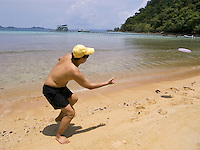 Thailand. Trat province. Ko Rang island. A thai man wearing a swimsuit and a yellow cap plays freesbee on the sand beach. Clear water. Ko Rang island is a natural park. 13.04.09 © 2009 Didier Ruef