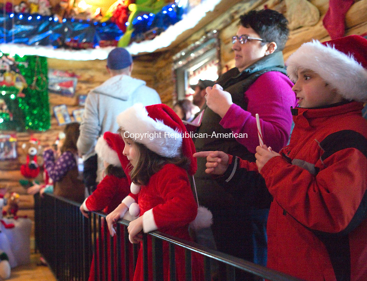 Torrington, CT- 06 December 2015-120615CM12-  Addie Plante, 6, center and her sister, Bailey, 6, left, and brother, Brady 8, all of Torrington  watch as elves prepare toys inside the toy shop at the Christmas Village in Torrington on Sunday.    Christopher Massa Republican-American