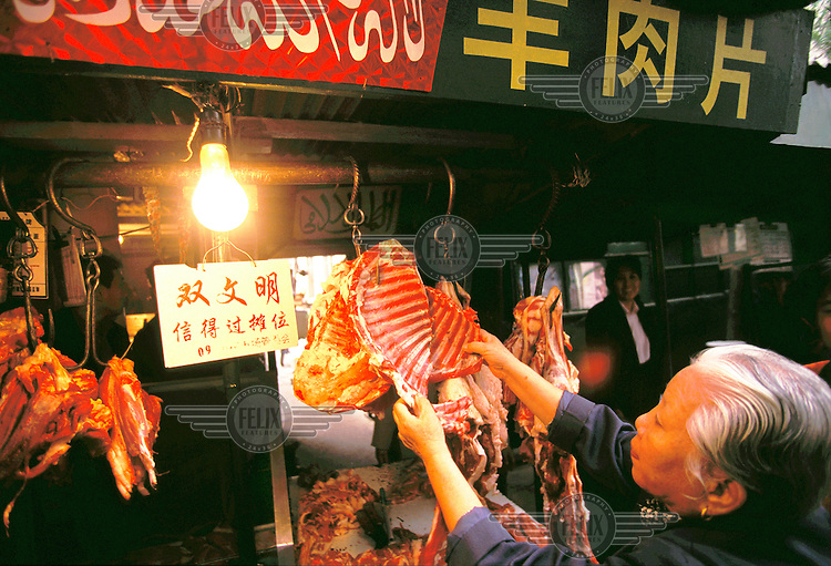 Mark Henley/Panos Pictures..China, Beijing..Custoimer at Muslim run butchers stall handling the meat.