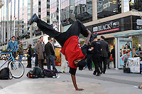 A young street dancer flying high beside The Toronto Eaton Centre at Yonge and Dundas, Toronto, Canada