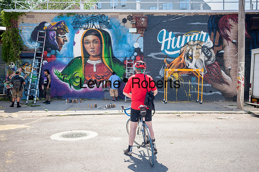 A bicyclist views the work of Juan and El Niño at the Welling Court Mural Project in the Astoria neighborhood of Queens in New York on Saturday, June 13, 2015. The annual neighborhood event decorates walls in this industrial part of Astoria. The project is crowd-funded and emerging street artists work side by side with established stars.  (© Richard B. Levine)